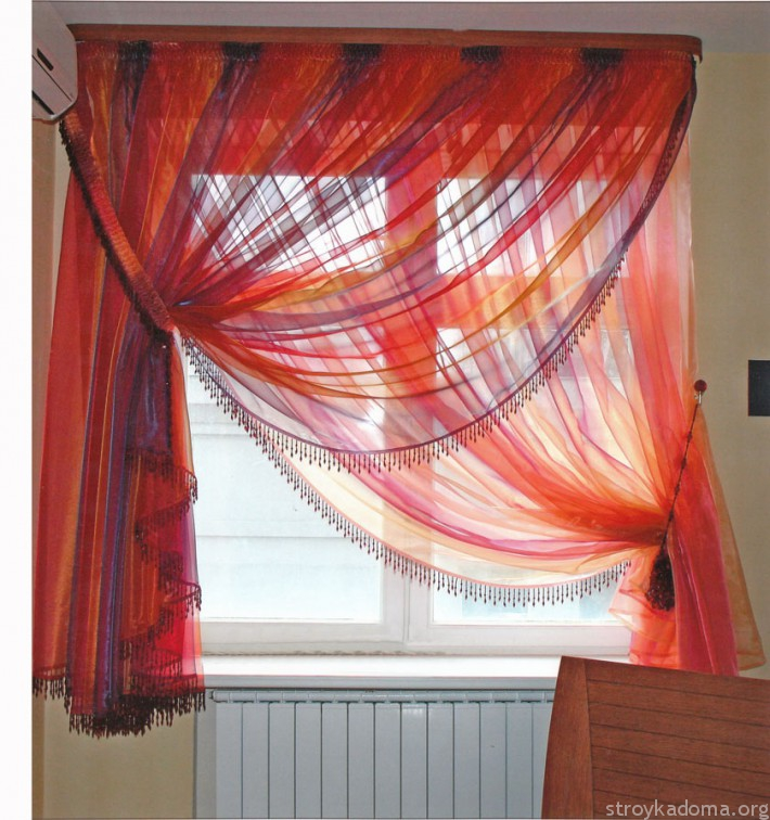 Полупрозрачная штора-плиссе легко прячется за цветной тюлевой занавеской.